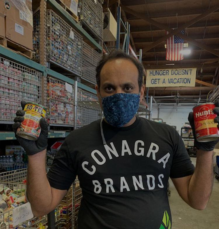 Man holding Hunt's and Ro*tel cans